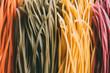 full frame image of arranged colorful raw tagliatelle pasta