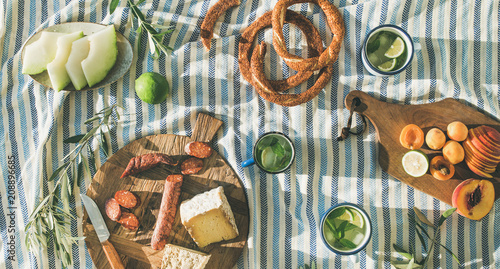 Flat-lay of summer picnic set with fruit, cheese, sausage, bagels and lemonade over striped blanket, top view