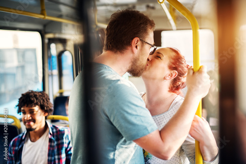Fototapeta Young adorable couple is displaying affection through the kiss while standing in a bus.