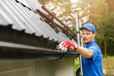 worker cleaning house gutter from leaves and dirt - 208897803