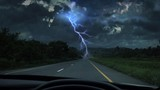 Front view while driving on the highway. Under heavy rain and lightning storms.