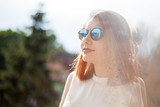 Portrait of gorgeous redhead young woman in summer rays with a reflextion - 208898025