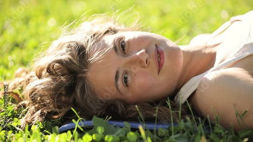 Wall mural Young woman lying on grass, turn face looking at camera and smile