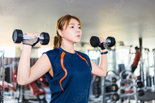 Poster Young Asian woman working out and doing fitness training at a local gym