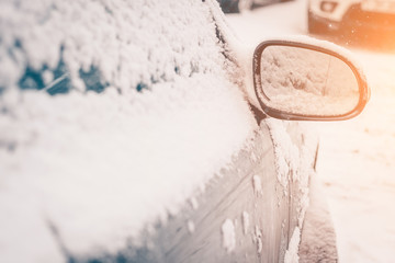 The arrival of spring in the cold snow-capped frosty countries, car mirrors under the snow