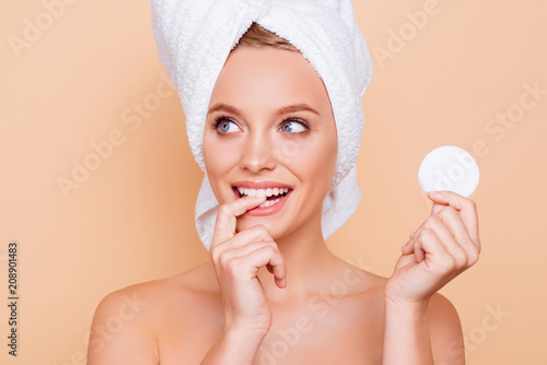 Leinwanddruck Bild Portrait of dreamy minded ponder girl with turban on head holding using white cotton pad for removing makeup isolated on beige background