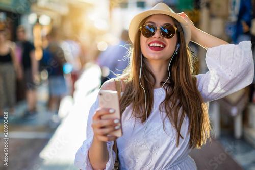 Junge, fröhliche, attraktive Frau in der Stadt beim Shoppen mit Telefon in der Hand