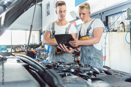 Experienced auto mechanic using a laptop for scanning and interpreting engine error codes next to an apprentice in a modern automobile repair shop