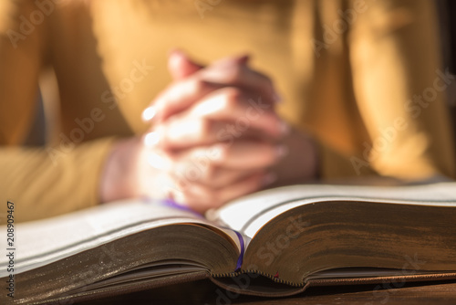 Woman praying with her hands over the bible, hard light