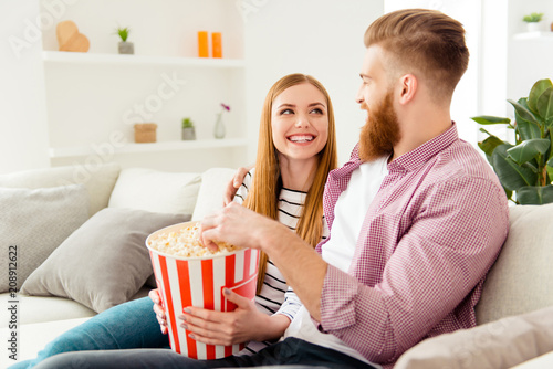 Leinwanddruck Bild Bearded hipster two partners friendship day lifestyle vacation hobby freetime happiness concept. Joyful rejoicing lovely people watching comedy together eating pop-corn from basket box on holidays