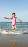 Bambina che salta in spiaggia ascoltando musica con le cuffie  - 208916856
