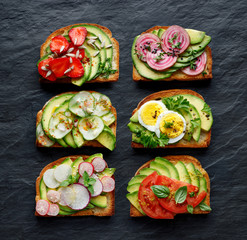 Avocado sandwiches, toasts with various vegetarian toppings on a black stone background, top view