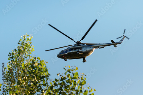 Fototapeta civil helicopter in the air against the sky and green tree