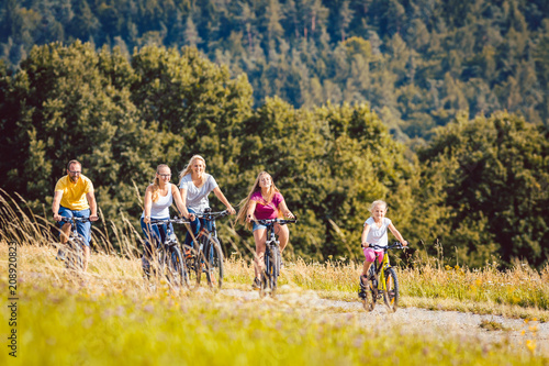 Leinwanddruck Bild Family riding their bicycles on afternoon in the summer countryside