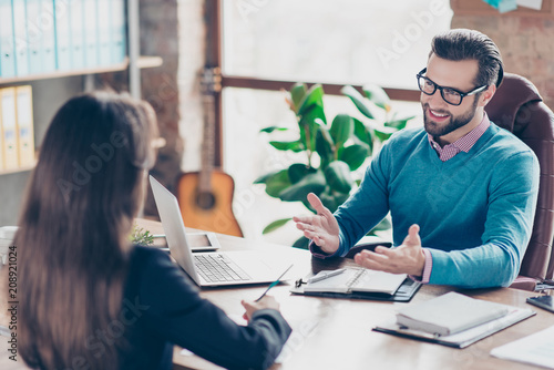 Job interview - Joyful, successful businessman asking candidate questions, sitting at desk in workplace on chair, girl making notes - 208921024