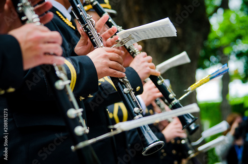 Many unrecognizable orchestra musicians playing musical instruments outdoors. Concept of a musical event - 208921273
