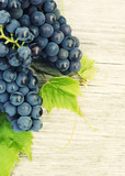 Blue grapes on an old wooden table, top view, copy space
