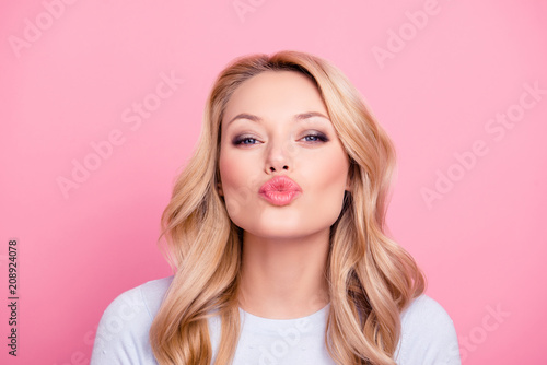 Leinwanddruck Bild Portrait of cute lovely girl in casual outfit with modern hairdo sending blowing kiss with pout lips looking at camera  isolated on pink background. Affection feelings concept