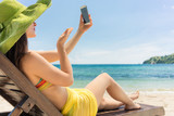 Attractive young woman sending online a love message through a selfie photo on the mobile phone while sitting on the beach during summer vacation
