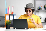 Young Man Working With Laptop and Drinking Orange Juice Wearing Fedora Hat on Summer Vacation Season at Office - 208926083