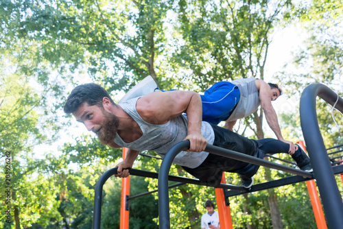 Low-angle view of a strong young man supporting his friend on his back, while doing extreme pull-ups during partner workout in a calisthenics park in summer - 208926262
