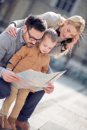 Leinwanddruck Bild Happy family with map are ready to travel
