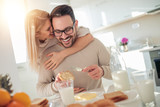Cheerful couple having breakfast in the kitchen - 208928207