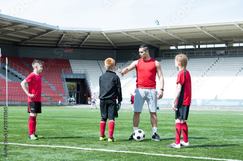 Full length portrait of Latin-American football coach teaching junior team boys in sunlit outdoor  stadium, copy space - 208931865