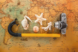 Sea shells, an old camera and a snorkel tube lie on a vintage map. Copy space. - 208933258