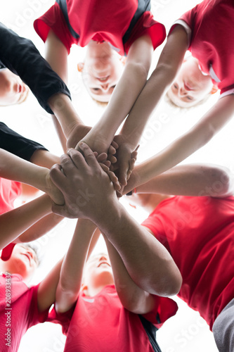 Foto Murales Low angle of junior football team stacking hands during motivational pep talk before match in outdoor stadium, copy space