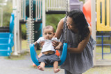 mother playing swing with  baby on  playground. - 208933692