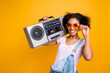 Leinwanddruck Bild - Portrait of fancy toothy girl with beaming smile in eyewear holding boom box on shoulder looking at camera isolated on yellow background. Music lover fan hobby concept