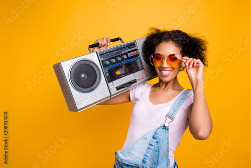 Leinwanddruck Bild Portrait of fancy toothy girl with beaming smile in eyewear holding boom box on shoulder looking at camera isolated on yellow background. Music lover fan hobby concept