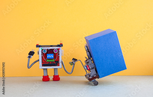 Robotic logistic delivery service concept. Robot moving big blue box container with powered pallet jack. Forklift cart mechanism on gray floor, yellow wall background. Copy space on cardboard box