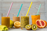 Four glasses of smoothies with straws and various fresh fruits