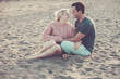 beautiful model couple caucasian young lady and man stay in love hugging and sitting on the beach. blonde and black hair in relationship outdoor leisure activity