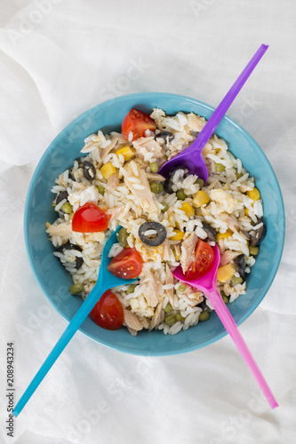 A baby blue bowl with cold rice salad with three spoons.