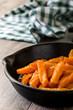 Sweet potato fries in iron pan on wooden table
