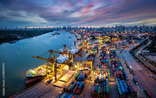 Leinwandbild Motiv Aerial view of international port with Crane loading containers in import export business logistics with cityscape of Bangkok city Thailand at night