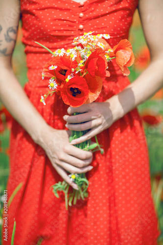 Fotobehang Rood beautiful woman in red dress standing in a poppy field holding flowers, close up on her hands with poppies, can be used as background