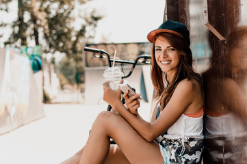 Stylish young brunette in a cap using phone.