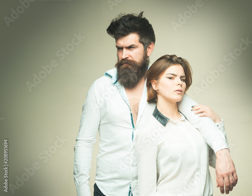 Barbershop concept. Fashion shot of couple after haircut. Woman on mysterious face with bearded man, light background. Man with stylish beard and mustache and girl with fresh haircut, new hairstyle