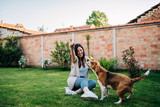 Fun time. Girl playing with her dog in the backyard. - 208952064