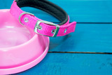 Pet collars and Bowls of pink on wooden background. - 208954644