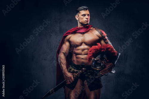 Brutal ancient Greece warrior with a muscular body in battle uniforms