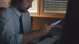 Businessman reading letter in dark interior, low key footage - 208959899