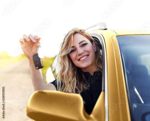 An attractive woman in the yellow car holds a car key in her hand.