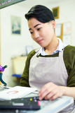 Portrait of young Asian woman drawing sketches sitting at table in glassworking studio - 208964022