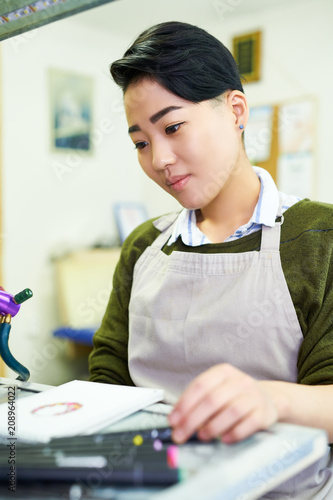 Portrait of young Asian woman drawing sketches sitting at table in glassworking studio