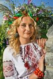 Beautiful  girl in national Ukrainian embroidery shirt and wreath of wild flowers. Holiday of Ivan Kupala in Ukraine. - 208966280